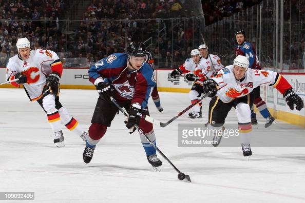 Kevin Porter of the Colorado Avalanche skates the puck into the offensive zone as Jay Bouwmeester and Olli Jokinen of the Calgary Flames try to...