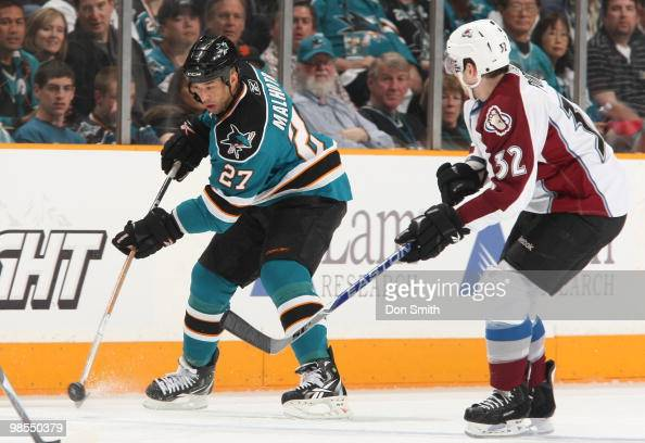 Kevin Porter of the Colorado Avalanche tries to block the pass of Manny Malhotra of the San Jose Sharks in Game One of the Western Conference...