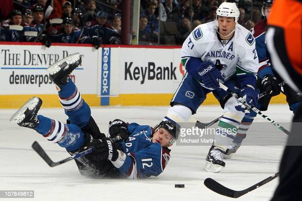 Kevin Porter of the Colorado Avalanche tries to maintain possesion after getting tripped up as Manny Malhotra of the Vancouver Canucks defends at the...