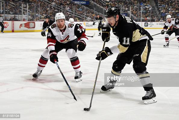 Kevin Porter of the Pittsburgh Penguins moves the puck past the defense of Klas Dahlbeck of the Arizona Coyotes during the first period at Consol...