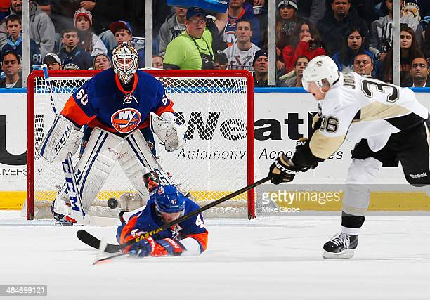 Kevin Poulin and Andrew MacDonald of the New York Islanders defend the net against Jussi Jokinen of the Pittsburgh Penguins at Nassau Veterans...