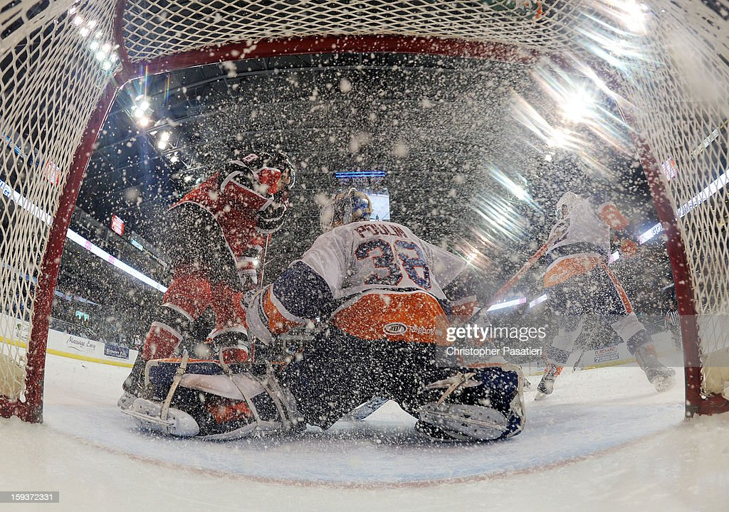 Kevin Poulin #38 of the Bridgeport Sound Tigers is sprayed with ice by Ethan Werek #8 of the Portland Pirates during an American Hockey League game on January 12, 2013 at the Webster Bank Arena at Harbor Yard in Bridgeport, Connecticut.