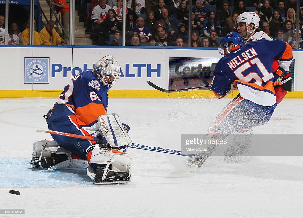 Kevin Poulin #60 of the New York Islanders and teammate <a gi-track='captionPersonalityLinkClicked' href=/galleries/search?phrase=Frans+Nielsen&family=editorial&specificpeople=634894 ng-click='$event.stopPropagation()'>Frans Nielsen</a> #51 defend the net against the Carolina Hurricanes at Nassau Veterans Memorial Coliseum on February 18, 2012 in Uniondale, New York. The Islanders defeated the Hurricanes 4-3.
