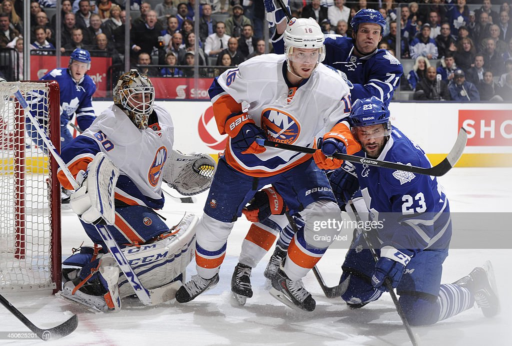 <a gi-track='captionPersonalityLinkClicked' href=/galleries/search?phrase=Kevin+Poulin&family=editorial&specificpeople=4952456 ng-click='$event.stopPropagation()'>Kevin Poulin</a> #60 of the New York Islanders defends the goal as teammate <a gi-track='captionPersonalityLinkClicked' href=/galleries/search?phrase=Peter+Regin&family=editorial&specificpeople=690589 ng-click='$event.stopPropagation()'>Peter Regin</a> #16 battles with David Clarkson #71 and Trevor Smith #23 of the Toronto Maple Leafs during NHL game action November 19, 2013 at the Air Canada Centre in Toronto, Ontario, Canada.