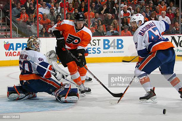 Kevin Poulin of the New York Islanders makes a kick save as teammate Andrew MacDonald defends against Michael Raffl of the Philadelphia Flyers on...