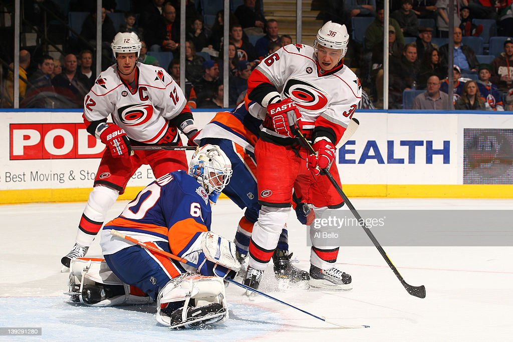 Kevin Poulin #60 of the New York Islanders makes a save against <a gi-track='captionPersonalityLinkClicked' href=/galleries/search?phrase=Jussi+Jokinen&family=editorial&specificpeople=570599 ng-click='$event.stopPropagation()'>Jussi Jokinen</a> #36 of the Carolina Hurricanes during their game on February 18, 2012 at the Nassau Coliseum in Uniondale, New York.
