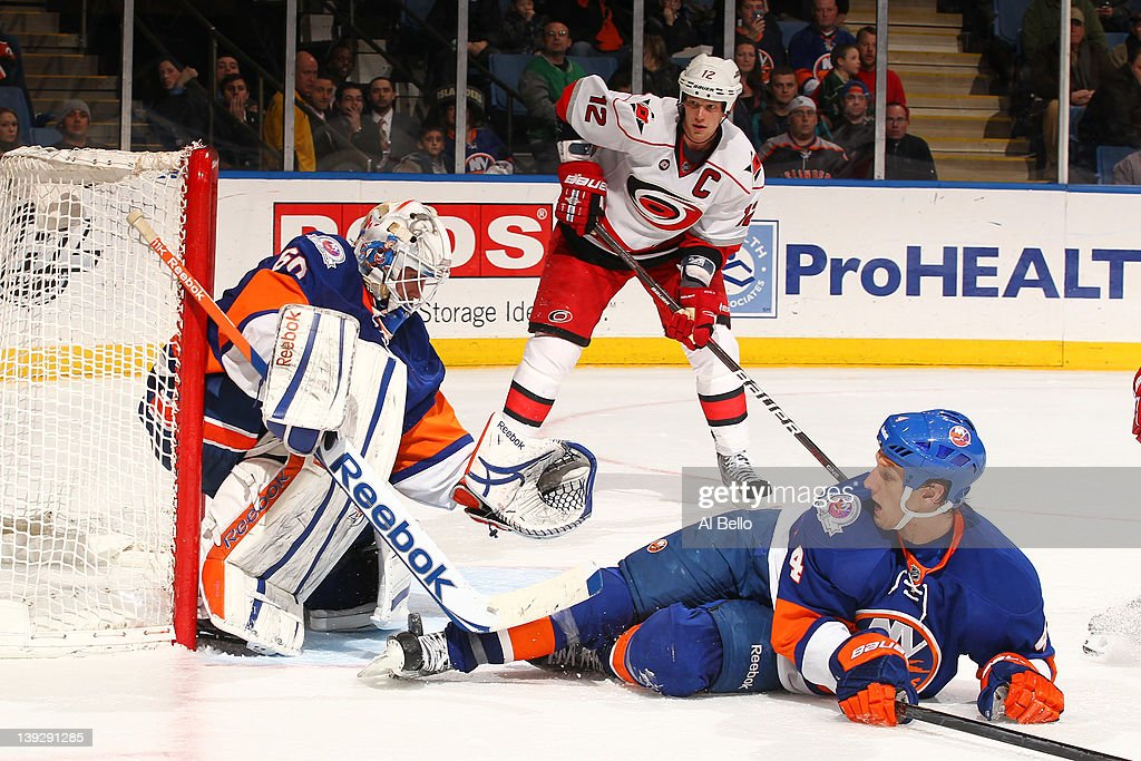 Kevin Poulin #60 of the New York Islanders makes a save as Mark Eaton #4 and <a gi-track='captionPersonalityLinkClicked' href=/galleries/search?phrase=Eric+Staal&family=editorial&specificpeople=202199 ng-click='$event.stopPropagation()'>Eric Staal</a> #12 of the Carolina Hurricanes look on during their game on February 18, 2012 at the Nassau Coliseum in Uniondale, New York.