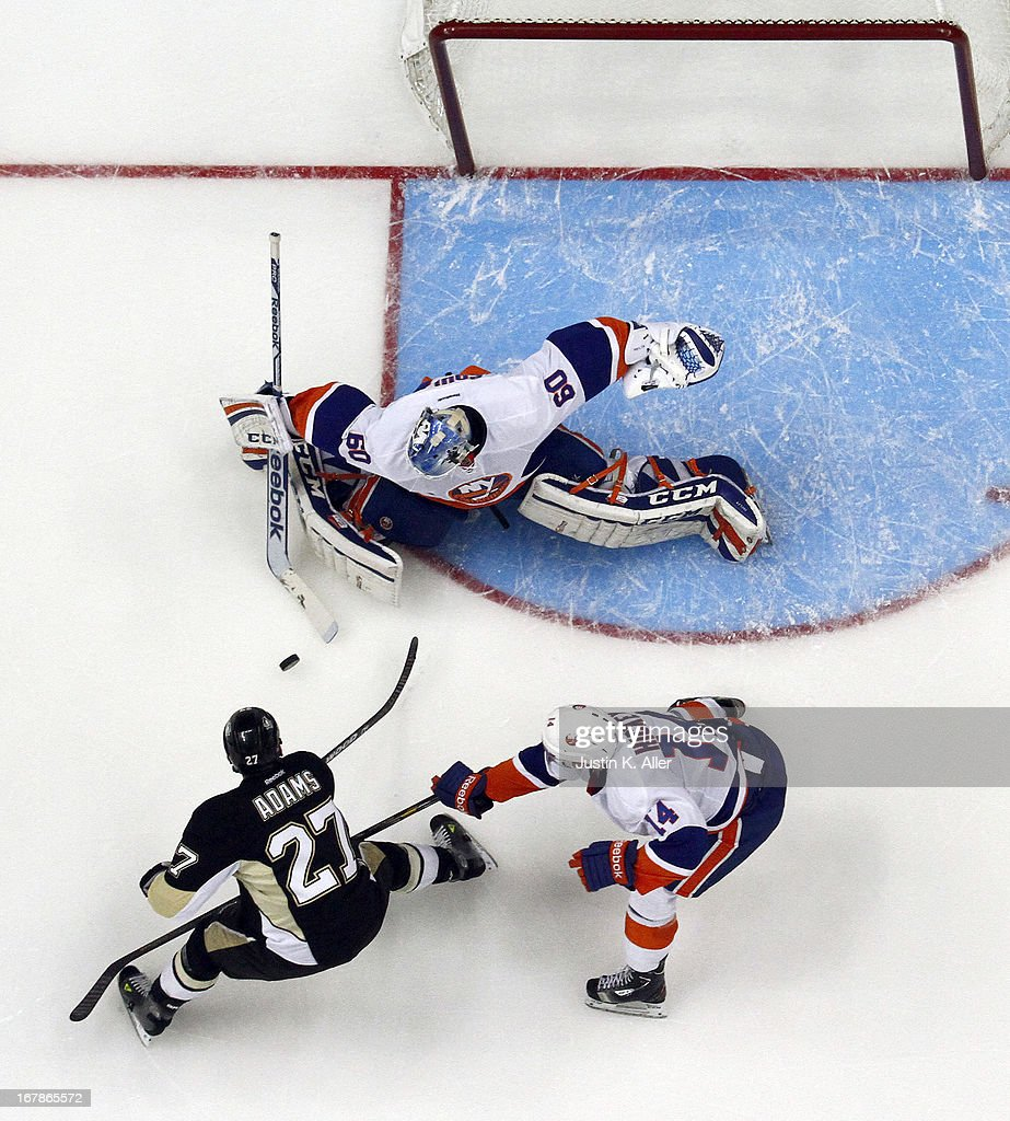 <a gi-track='captionPersonalityLinkClicked' href=/galleries/search?phrase=Kevin+Poulin&family=editorial&specificpeople=4952456 ng-click='$event.stopPropagation()'>Kevin Poulin</a> #60 of the New York Islanders makes a save on <a gi-track='captionPersonalityLinkClicked' href=/galleries/search?phrase=Craig+Adams&family=editorial&specificpeople=211144 ng-click='$event.stopPropagation()'>Craig Adams</a> #27 of the Pittsburgh Penguins in Game One of the Eastern Conference Quarterfinals during the 2013 NHL Stanley Cup Playoffs at Consol Energy Center on May 1, 2013 in Pittsburgh, Pennsylvania. The Penguins won 5-0.