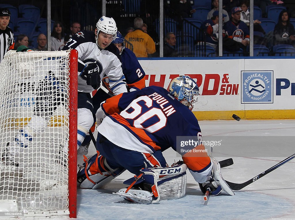 Kevin Poulin #60 of the New York Islanders makes the save as Eric Tangradi #27 of the Winnipeg Jets looks for the rebound at the Nassau Veterans Memorial Coliseum on April 2, 2013 in Uniondale, New York.
