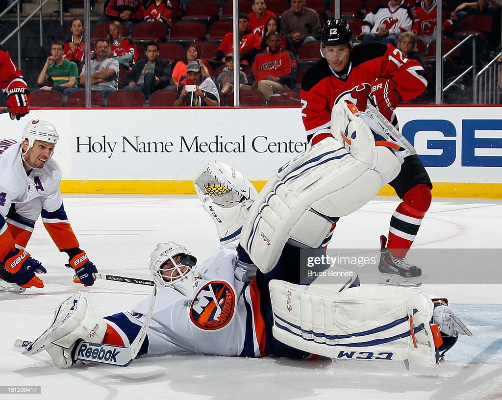 <a gi-track='captionPersonalityLinkClicked' href=/galleries/search?phrase=Kevin+Poulin&family=editorial&specificpeople=4952456 ng-click='$event.stopPropagation()'>Kevin Poulin</a> #60 of the New York Islanders makes the second period save as <a gi-track='captionPersonalityLinkClicked' href=/galleries/search?phrase=Damien+Brunner&family=editorial&specificpeople=6931570 ng-click='$event.stopPropagation()'>Damien Brunner</a> #12 of the New Jersey Devils looks for the rebound at the Prudential Center on September 19, 2013 in Newark, New Jersey.