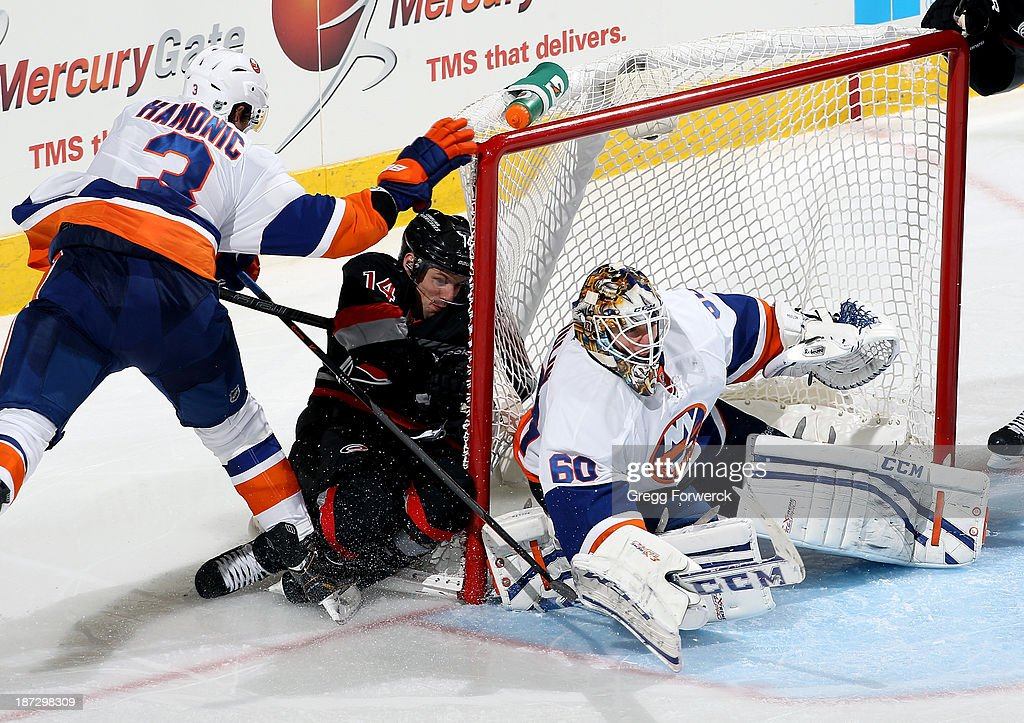 Kevin Poulin #60 of the New York Islanders reacts to a shot as Travis Hamonic #3 trips up Nathan Gerbe #14 of the Carolina Hurricanes in the net during their NHL game at PNC Arena on November 7, 2013 in Raleigh, North Carolina.
