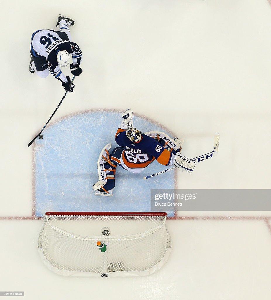 Kevin Poulin of the New York Islanders tends net against Matt Halischuk of the Winnipeg Jets at the Nassau Veterans Memorial Coliseum on November 27...