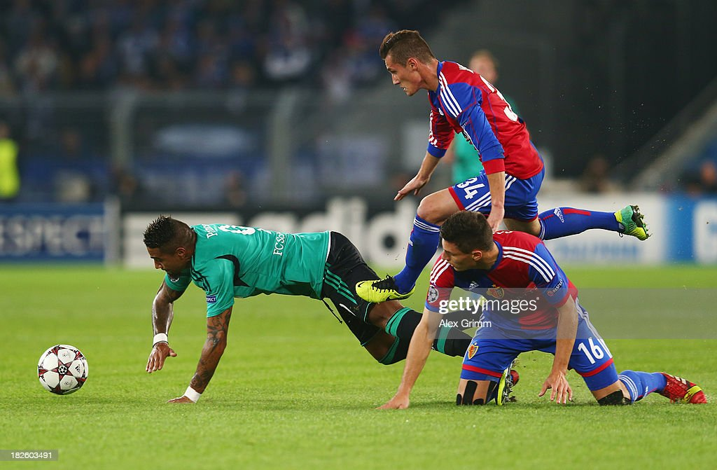 Kevin Prince Boateng of Schalke is challenged by Fabian Schaer (front) and Taulant Xhaka of Basel during the UEFA Champions League Group E match between FC Basel 1893 and FC Schalke 04 at St. Jakob-Park on October 1, 2013 in Basel, Switzerland.
