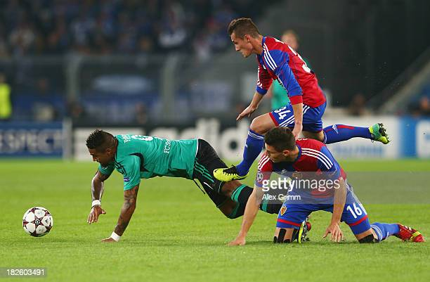 Kevin Prince Boateng of Schalke is challenged by Fabian Schaer and Taulant Xhaka of Basel during the UEFA Champions League Group E match between FC...