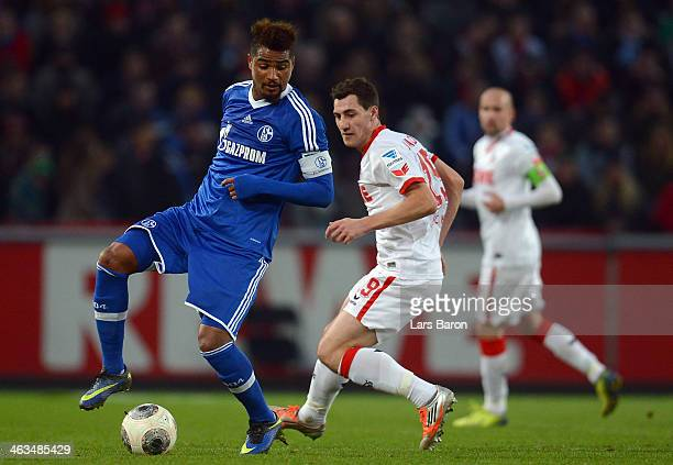 Kevin Prince Boateng of Schalke is challenged by Mato Jajalo of Koeln during a test match between 1 FC Koeln and FC Schalke 04 at RheinEnergieStadion...