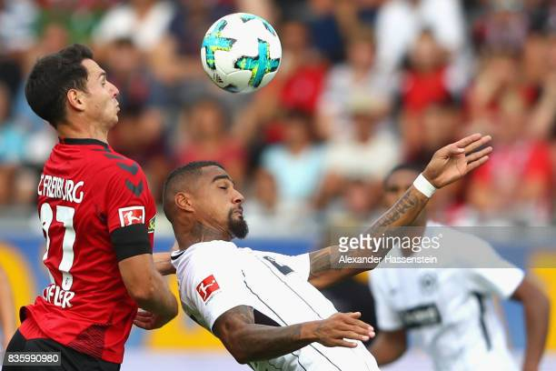 Kevin PrinceBoateng of Frankfurt battles for the ball with Nicolas Hoefler of Freiburg during the Bundesliga match between SportClub Freiburg and...