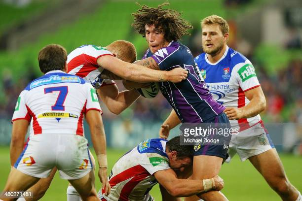 Kevin Proctor of the Storm is tackled by Knights players during the round three NRL match between the Melbourne Storm and the Newcastle Knights at...