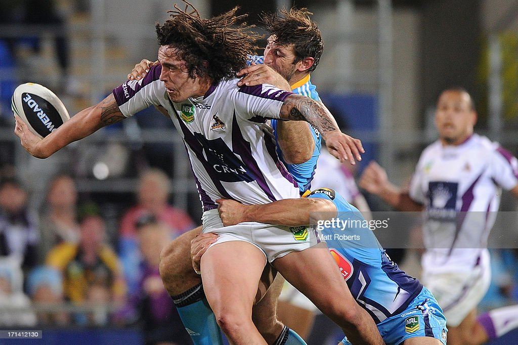 Kevin Proctor of the Storm offloads in the tackle during the round 15 NRL match between the Gold Coast Titans and the Melbourne Storm at Skilled Park on June 24, 2013 on the Gold Coast, Australia.