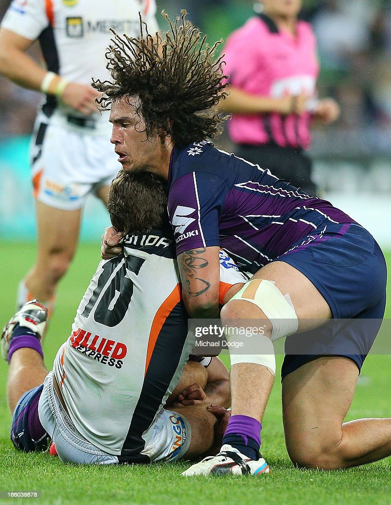 Kevin Proctor of the Storm tackles Matt Bell of the Tigers during the round 5 NRL match between the Melbourne Storm and the Wests Tigers at AAMI Stadium on April 8, 2013 in Melbourne, Australia.