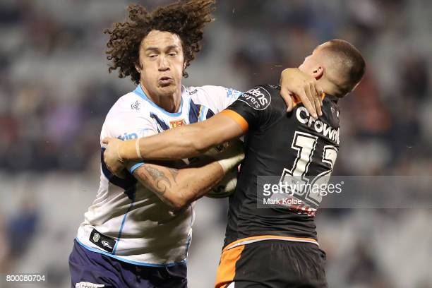 Kevin Proctor of the Titans is tackled by Kyle Lovett of the Tigers during the round 16 NRL match between the Wests Tigers and the Gold Coast Titans...