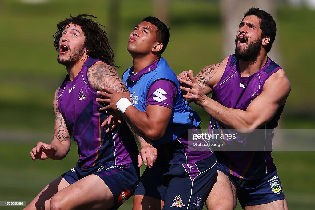Kevin Proctor (L) Richard Kennar (C) and Jesse Bromwich contest for an AFL football during a Melbourne Storm NRL training session at Gosch's Paddock on August 22, 2014 in Melbourne, Australia.
