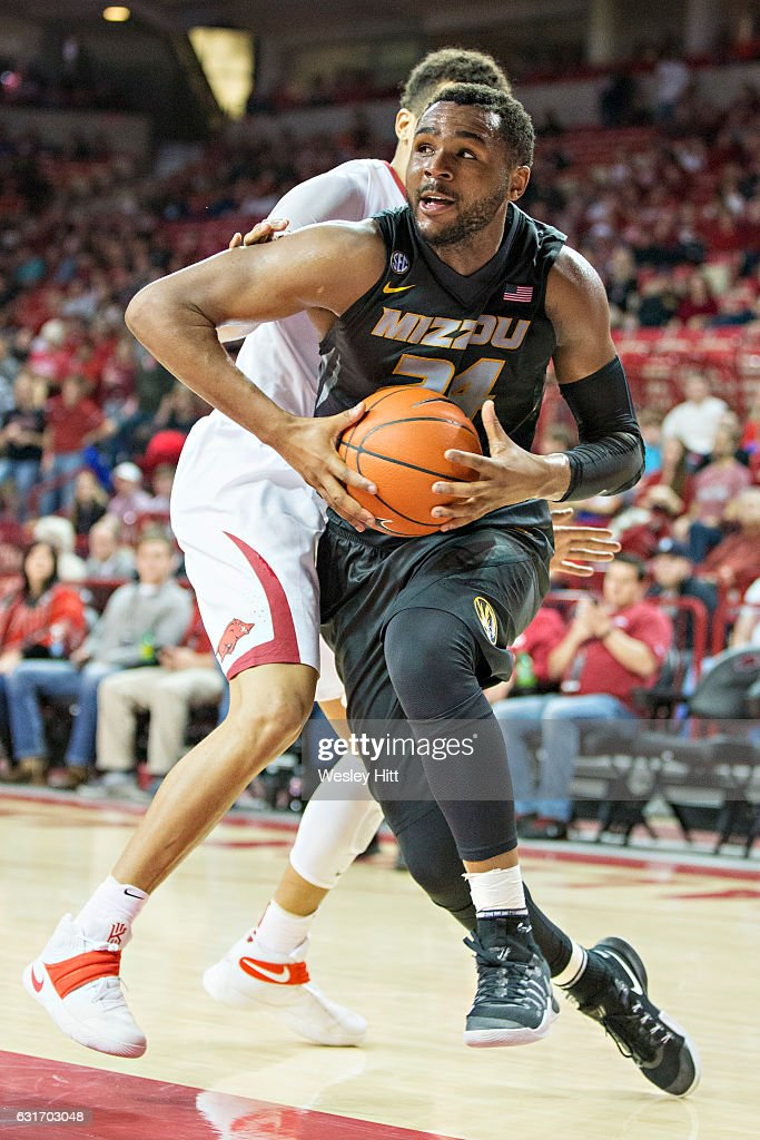 Kevin Puryear #24 of the Missouri Tigers drives to the basket past Dustin Thomas #13 of the Arkansas Razorbacks at Bud Walton Arena on January 14, 2017 in Fayetteville, Arkansas. The Razorbacks defeated the Tigers 92-73.