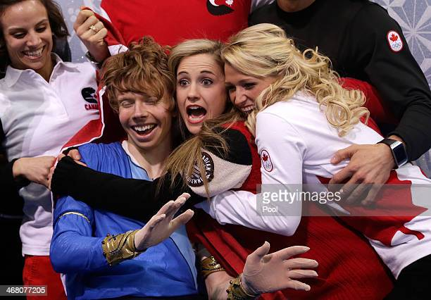 Kevin Reynolds of Canada reacts with teammates and coaches after receiving his score in the Men's Figure Skating Men's Free Skate during day two of...