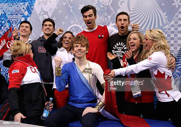 Kevin Reynolds of Canada reacts with teammates and coaches while waiting for his score in the Men's Figure Skating Men's Free Skate during day two of...
