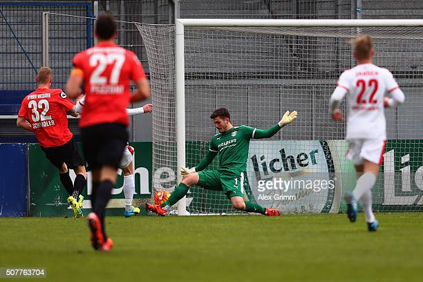 Kevin Schindler of Wehen Wiesbaden scores his team's first goal against goalkeeper Fabian Bredlow of Halle during the Third League match between SV...