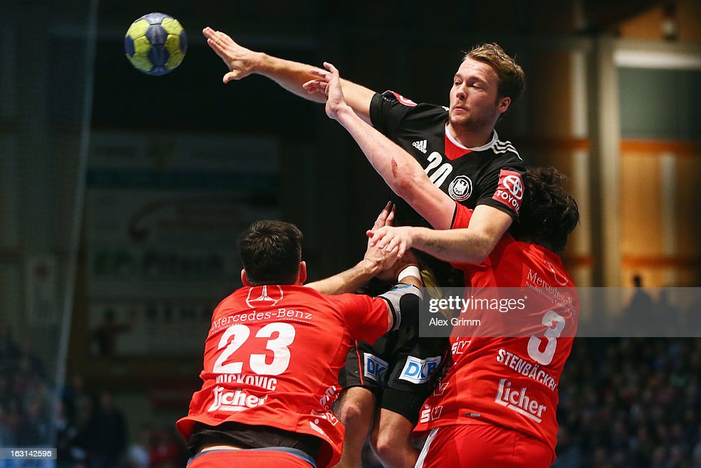 Kevin Schmidt (back) of Germany is challenged by Nenad Vuckovic (L) and Jonathan Stenbacken of Melsungen during a benefit match between the German national handball team and MT Melsungen at Rothenbach-Halle on March 5, 2013 in Kassel, Germany.
