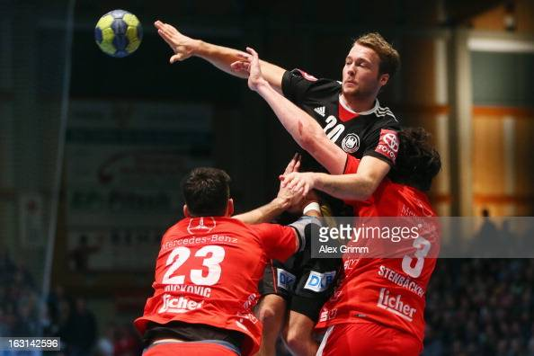 Kevin Schmidt of Germany is challenged by Nenad Vuckovic and Jonathan Stenbacken of Melsungen during a benefit match between the German national...
