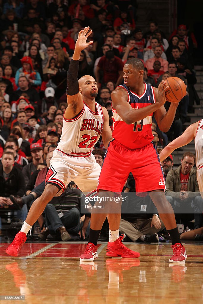 Kevin Seraphin #13 of the Washington Wizards controls the ball against Taj Gibson #22 of the Chicago Bulls on December 29, 2012 at the United Center in Chicago, Illinois.