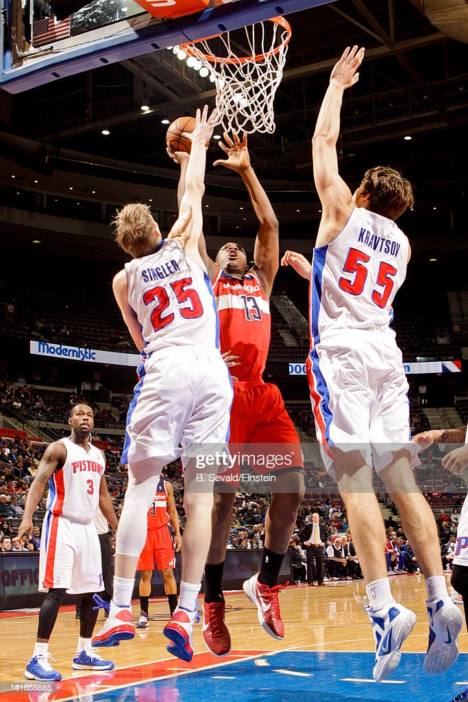 Kevin Seraphin #13 of the Washington Wizards drives to the basket against Kyle Singler #25 and Viacheslav Kravtsov #55 of the Detroit Pistons on February 13, 2013 at The Palace of Auburn Hills in Auburn Hills, Michigan.