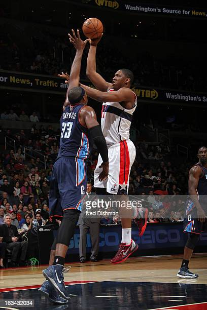 Kevin Seraphin of the Washington Wizards shoots against Brendan Haywood of the Charlotte Bobcats during the game at the Verizon Center on March 9...