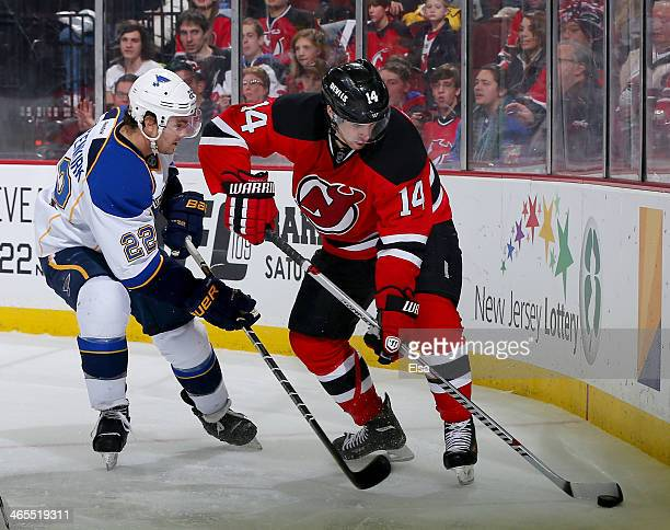Kevin Shattenkirk of the St Louis Blues and Adam Henrique of the New Jersey Devils fight for the puck at Prudential Center on January 21 2014 in...