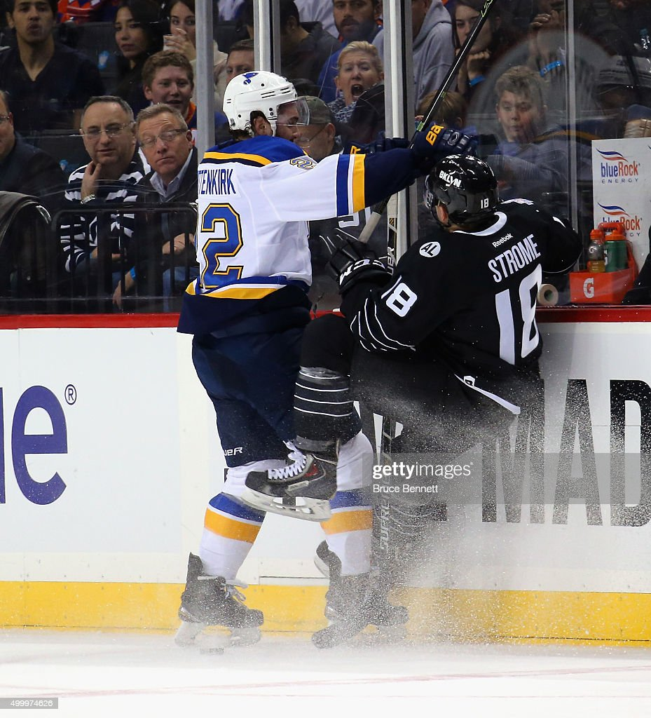 Kevin Shattenkirk #22 of the St. Louis Blues checks Ryan Strome #18 of the New York Islanders during the first period at the Barclays Center on December 4, 2015 in Brooklyn borough of New York City.