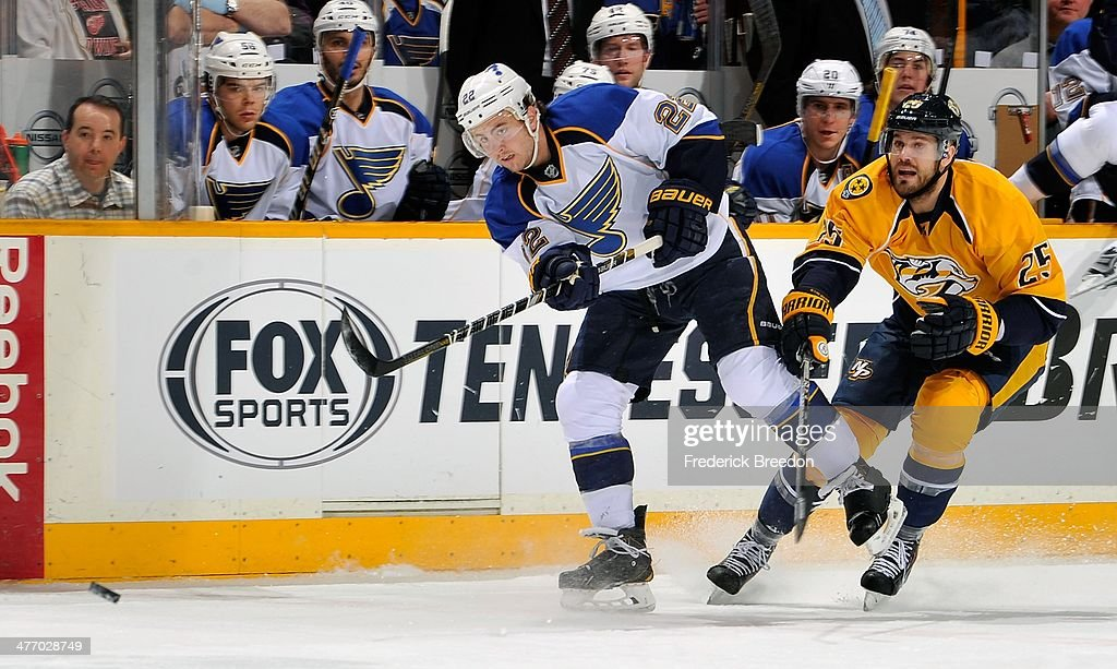 Kevin Shattenkirk #22 of the St. Louis Blues dumps a puck past Vicktor Stalberg #25 of the Nashville Predators at Bridgestone Arena on March 6, 2014 in Nashville, Tennessee.