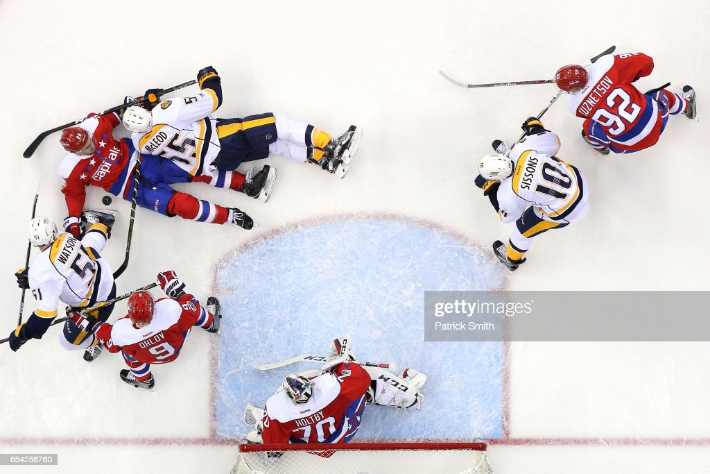 Kevin Shattenkirk #22 of the Washington Capitals and Cody McLeod #55 of the Nashville Predators battle for the puck during the second period at Verizon Center on March 16, 2017 in Washington, DC.