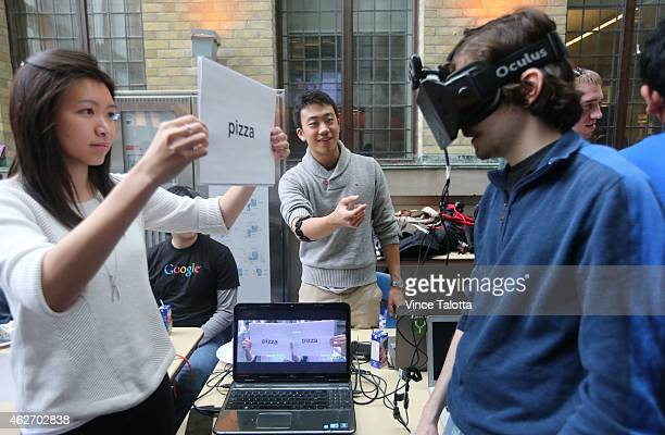 Kevin Shi wearing a myo armband with the help of Karina Mio holding a word card and Alex Labach wearing a pair of oculus rift all from Waterloo...