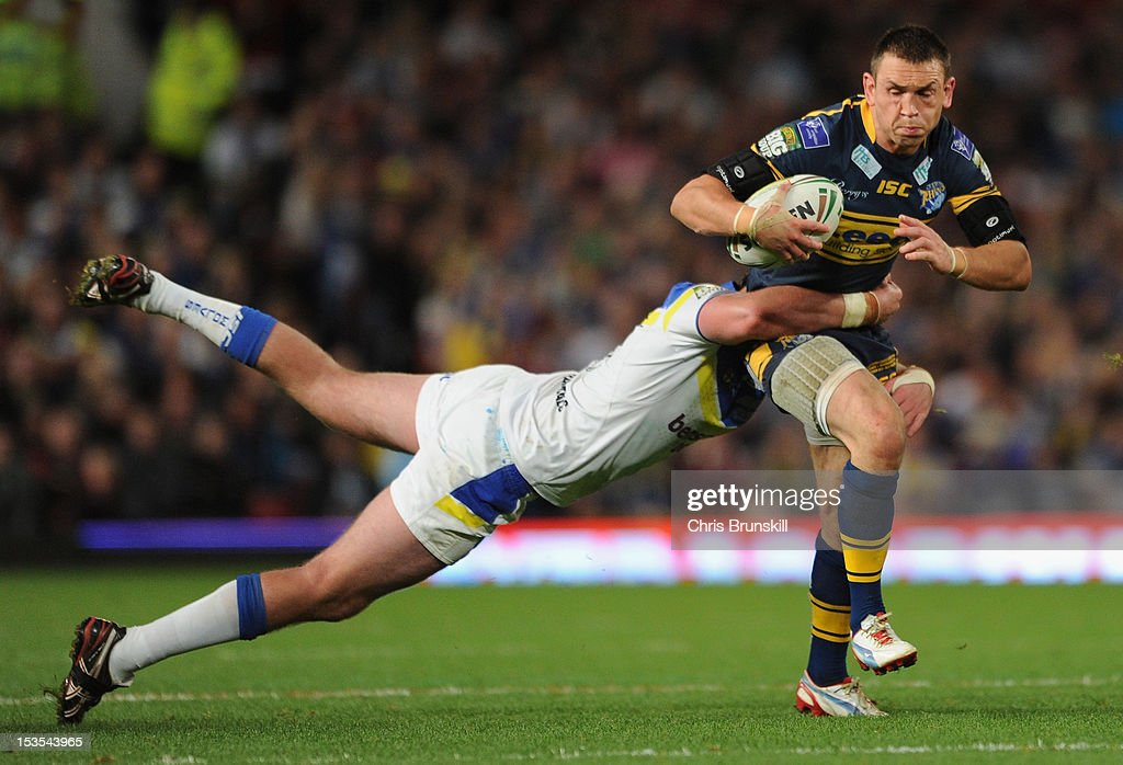 <a gi-track='captionPersonalityLinkClicked' href=/galleries/search?phrase=Kevin+Sinfield&family=editorial&specificpeople=240224 ng-click='$event.stopPropagation()'>Kevin Sinfield</a> of Leeds Rhinos is tackled by <a gi-track='captionPersonalityLinkClicked' href=/galleries/search?phrase=Trent+Waterhouse&family=editorial&specificpeople=210528 ng-click='$event.stopPropagation()'>Trent Waterhouse</a> of Warrington Wolves during the Stobart Super League Grand Final between Warrington Wolves and Leeds Rhinos at Old Trafford on October 6, 2012 in Manchester, England.