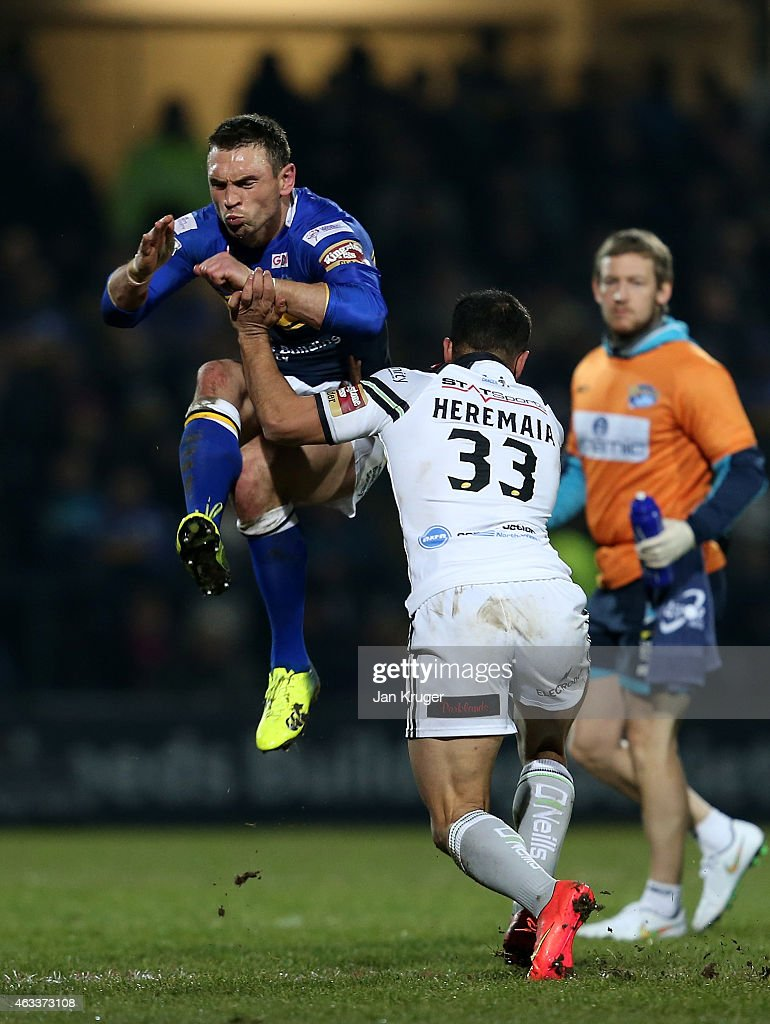 Kevin Sinfield of Leeds Rhinos kicks under pressure from Aaron Heremaia of Widnes Vikings during the First Utility Super League match between Leeds Rhinos and Widnes Vikings at Headingley Carnegie Stadium on February 13, 2015 in Leeds, England.