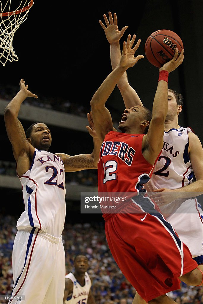 Kevin Smith #12 of the Richmond Spiders goes to the basket against Marcus Morris #22 of the Kansas Jayhawks during the southwest regional of the 2011 NCAA men's basketball tournament at the Alamodome on March 25, 2011 in San Antonio, Texas.