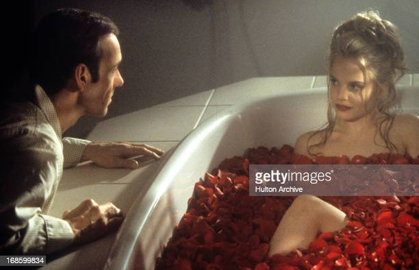 Kevin Spacey looks at Mena Suvari as she bathes in rose pedals in a scene from the film 'American Beauty' 1999