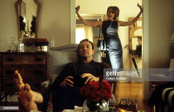 Kevin Spacey lounging in a reclining chair as Annette Bening stands in the entryway perturbed in a scene from the film 'American Beauty' 1999