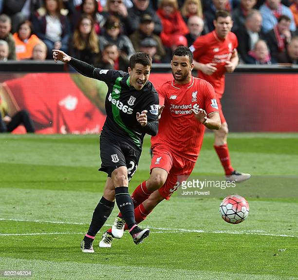 Kevin Stewart of Liverpool competes with Bojan Krkic of Stoke City during the Barclays Premier League match between Liverpool and Stoke City at...