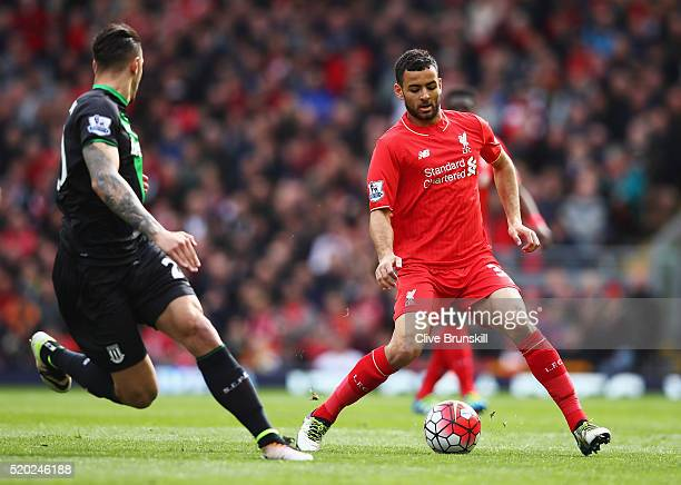 Kevin Stewart of Liverpool is watched by Geoff Cameron of Stoke City during the Barclays Premier League match between Liverpool and Stoke City at...
