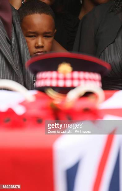 Kevin the son of Lance Sergeant Dale McCallum of 1st Battalion Scots Guards watches as pallbearers carry his fathers coffin out of the New Testament...