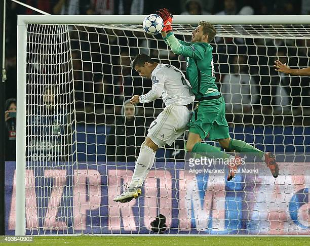 Kevin Trapp of Paris SaintGermain competes for the ball with Cristiano Ronaldo of Real Madrid during the UEFA Champions League Group A match between...