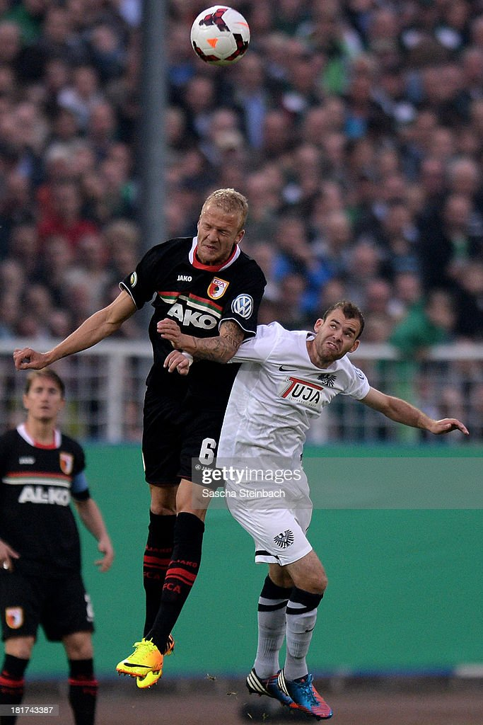 Kevin Vogt of Augsburg and Amaury Bischoff of Muenster compete for a header during DFB Cup second round match between Preussen Muenster and FC Augsburg at Preussenstadion on September 24, 2013 in Muenster, Germany.