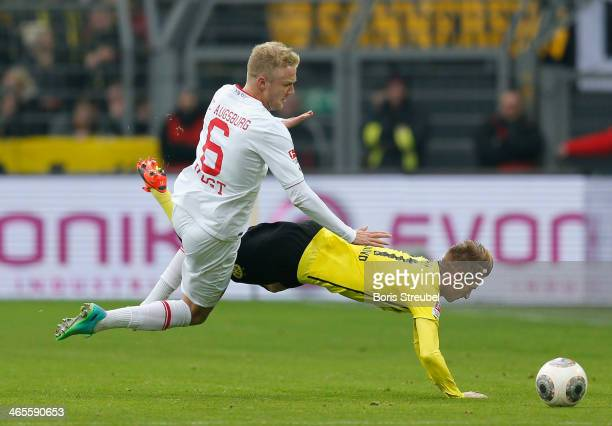 Kevin Vogt of Augsburg fights for the ball with Marco Reus of Dortmund during the Bundesliga match between Borussia Dortmund and FC Augsburg at...